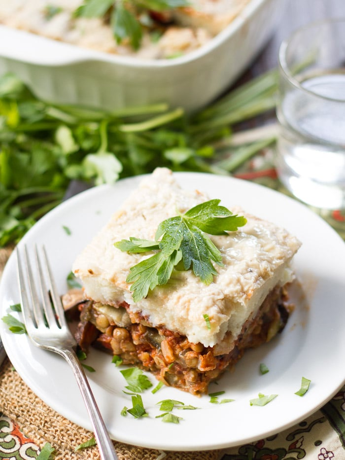 Vegan Eggplant Moussaka on a Plate with Casserole Dish and Water Glass in the Background