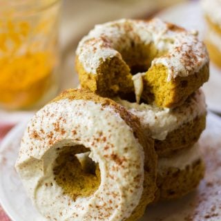 Stack of Vegan Golden Milk Doughnuts with a Jar of Turmeric in the Background