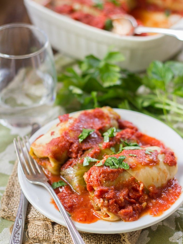 Quinoa & Lentil Stuffed Vegan Cabbage Rolls on a Plate with Water Glass and Casserole Dish in the Background