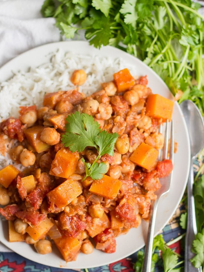 Overhead View of a Plate of Butternut Squash Chana Masala and Rice Surrounded by Fresh Cilantro
