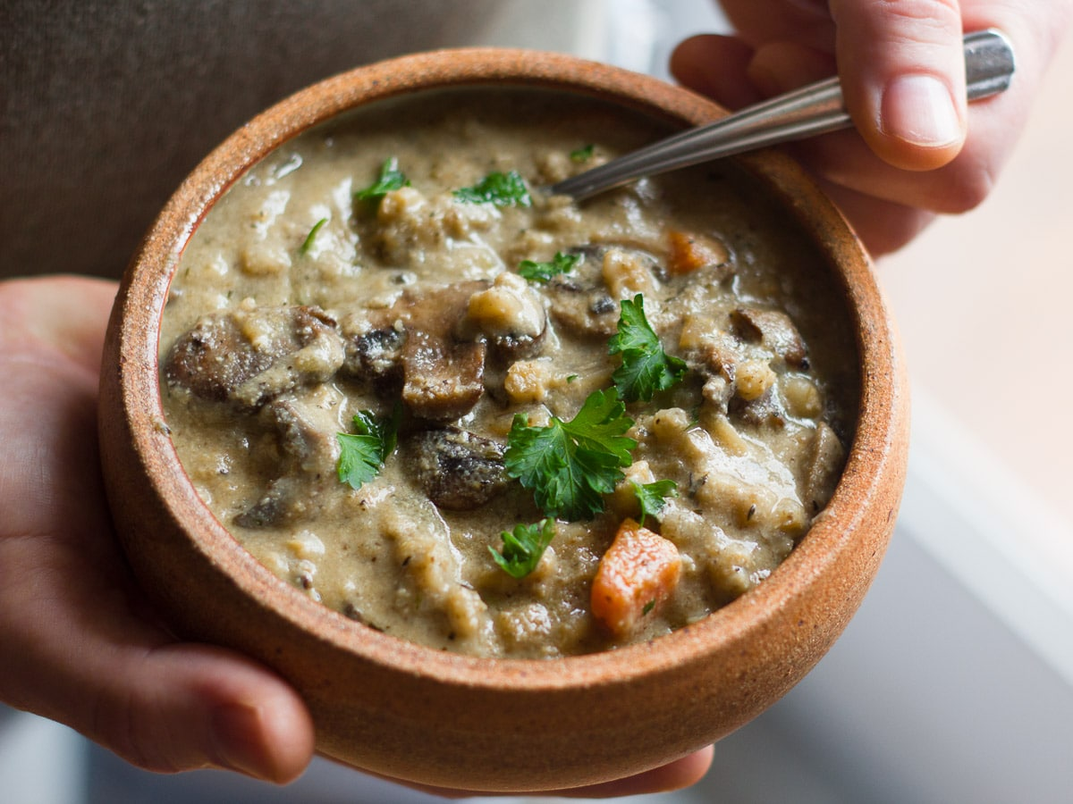 Hands Holding a Bowl of Creamy Vegan Mushroom Barley Soup with Spoon