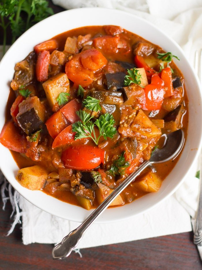 Bowl of Eggplant Goulash with Spoon Sitting on a Napkin on a Wooden Surface