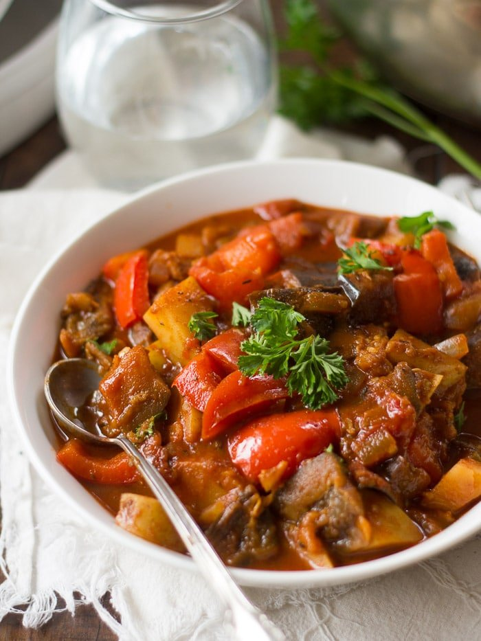 Close Up of a Bowl of Eggplant Goulash with Spoon and Sprig of Parsley on Top