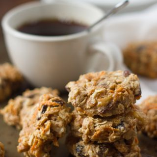 Stack of 3 Morning Glory Breakfast Cookies with a Fourth Cookie Leaning Against the Stack, Coffee Cup in the Background
