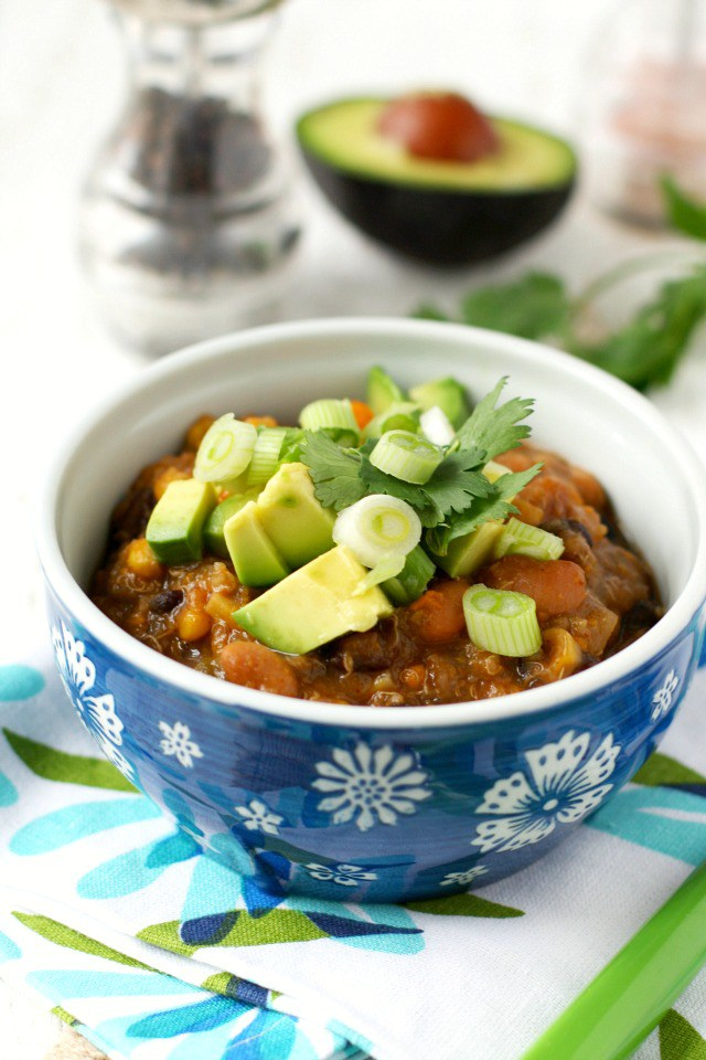 Sweet Potato Quinoa Chili in a Blue Bowl with Pepper Shaker and Avocado Half in the Background