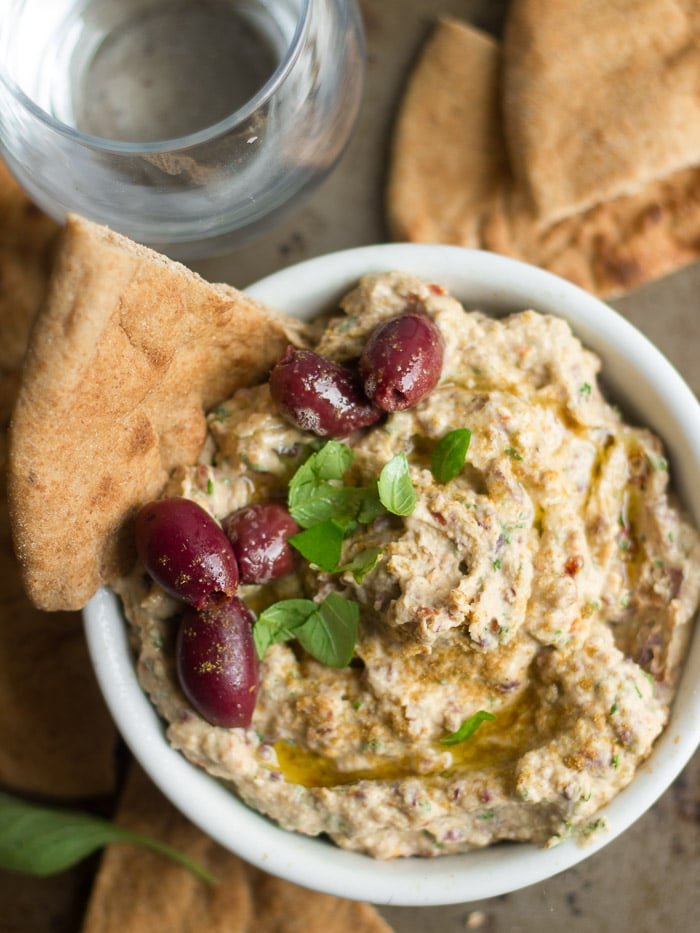 Bowl of Sun-Dried Tomato & Kalamata Olive Hummus with Olives and basil on Top, Pita Wedges and Water Glass on the Side