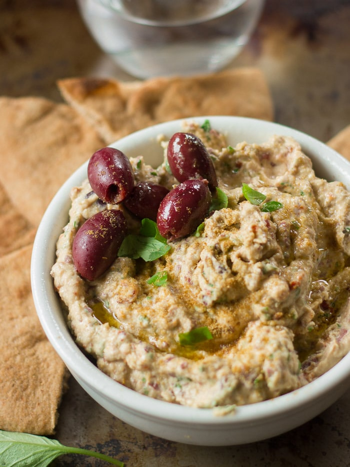 Close Up of a Bowl of Sun-Dried Tomato & Kalamata Olive Hummus with Pita Bread in the Background