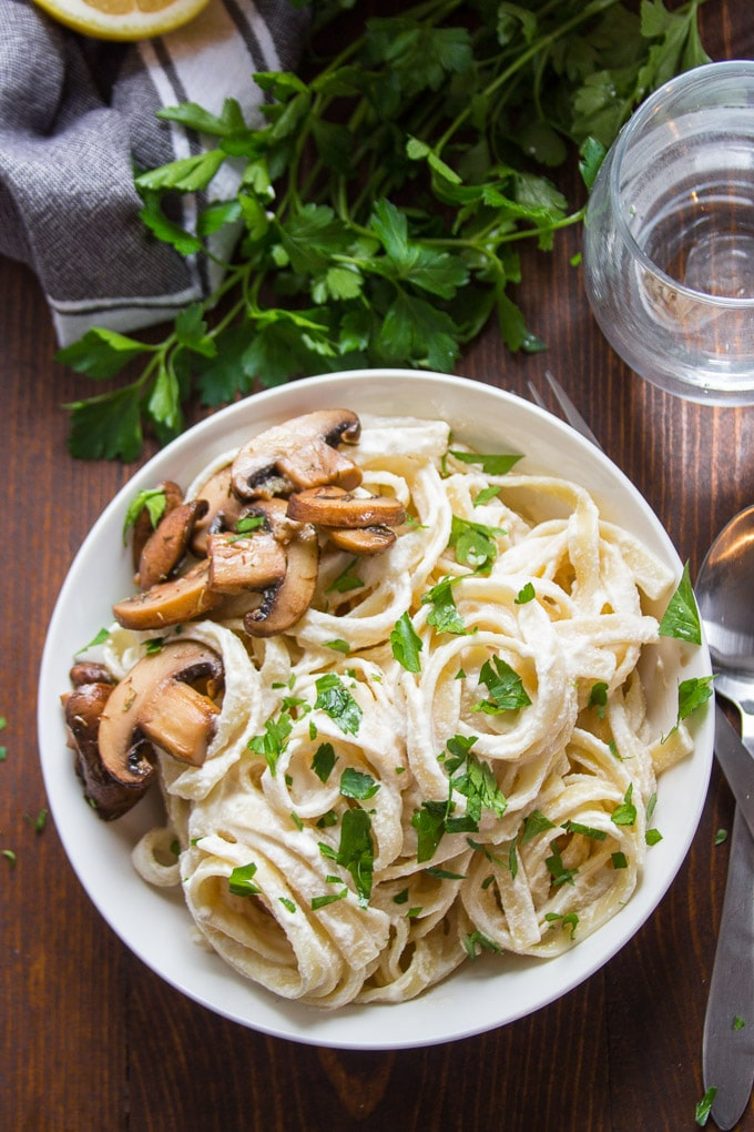 Vegan Fettuccine Alfredo in a Bowl with Fork, Spoon and Water Glass