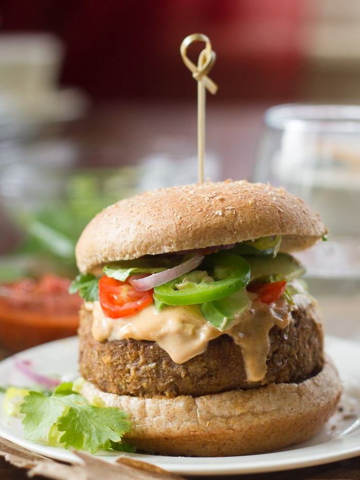 Vegan Lentil Nacho Burger Topped with Tahini Cheese, Tomato Slices, Onions and Jalapenos on a Plate