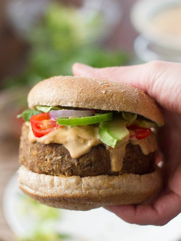 Close Up of a Hand Holding a Vegan Lentil Nacho Burger