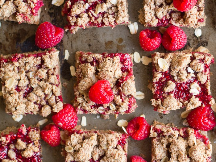 Almond Butter Raspberry Chia Jam Bars and Raspberries Arranged on a Distressed Baking Sheet