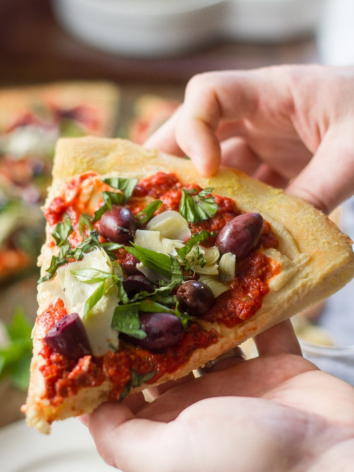 Close Up of a Pair of Hands Holding a Slice of Vegan Greek Pizza