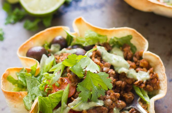 Two Tortilla Bowls Filled with Lentil Walnut Vegan Taco Salad with Lime Slices in the Background