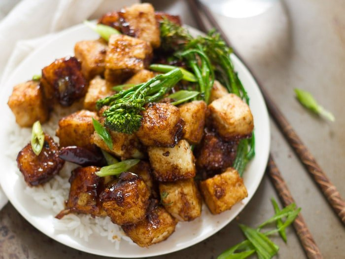 Close Up of Crispy Black Pepper Tofu and Broccolini on a Plate with Rice
