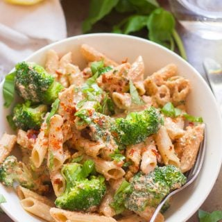 Bowl of Creamy Vegan Sun-Dried Tomato Pasta with Broccoli with Basil, Lemon Half, and Water Glass in the Background