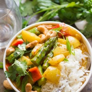 Bowl of Golden Spring Vegetable Thai Curry and Rice with Water Glass and Cilantro in the Background