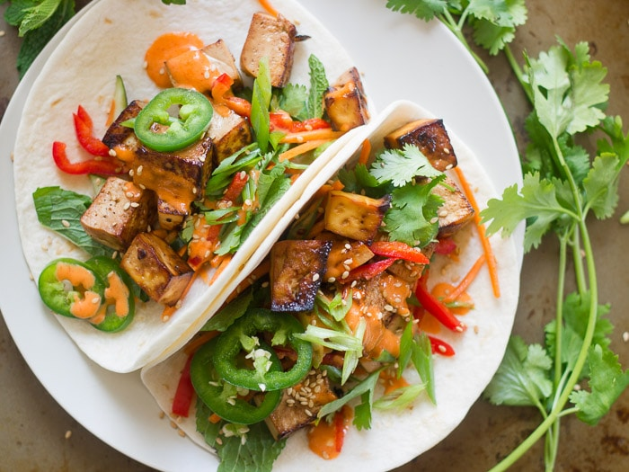 Overhead View of Two Smoky Tofu Banh Mi Tacos on a Plate Surrounded By Fresh Cilantro
