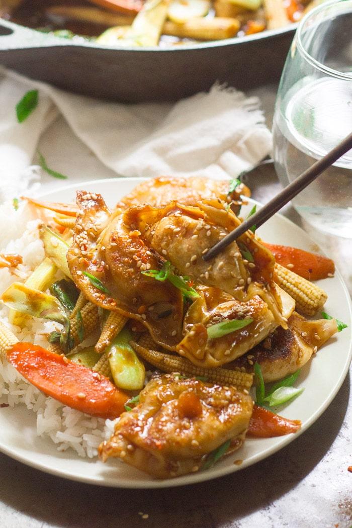 Pair of Chopsticks Grabbing a Dumpling From a Plate of Stir-Fry