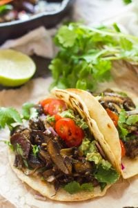 Two Mushroom Carnitas Tacos with a Lime Half and Cilantro in the Background