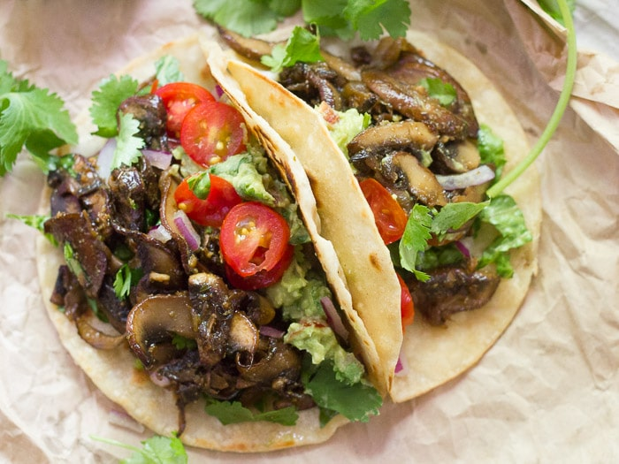 Two Mushroom Carnitas Tacos Surrounded By Cilantro Sprigs