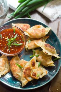Plate of Smoky Tofu Dumplings with a Bowl of Sweet Chili Dipping Sauce, Water Glass and Scallions in the Background