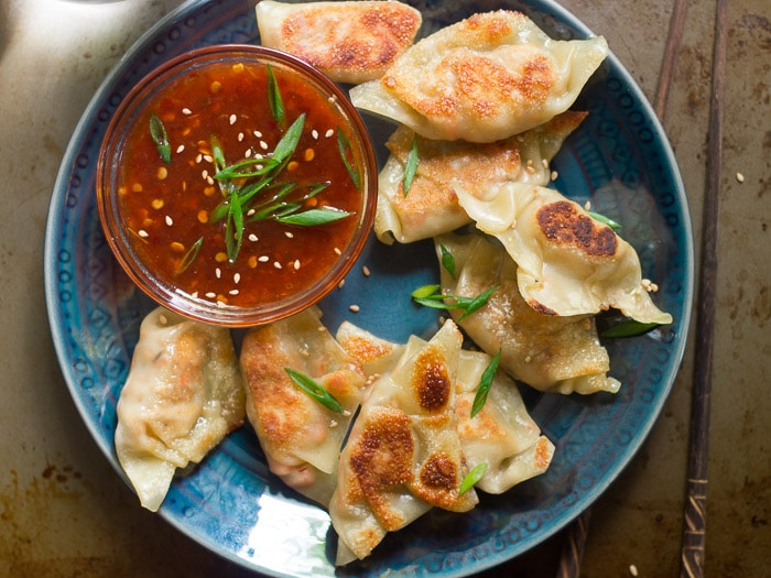 Overhead View of a Plate of Smoky Tofu Dumplings with a Bowl of Sweet Chili Dipping Sauce