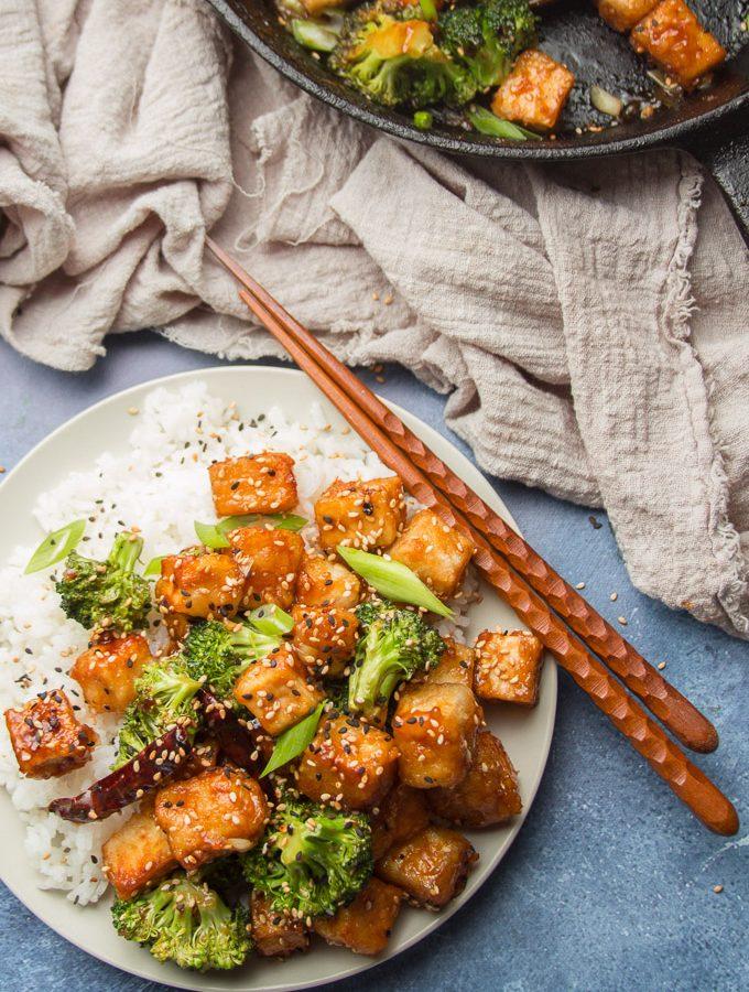Plate of General Tso's Tofu, Chopsticks, Tea Towel and Cast Iron Skillet on a Blue Background