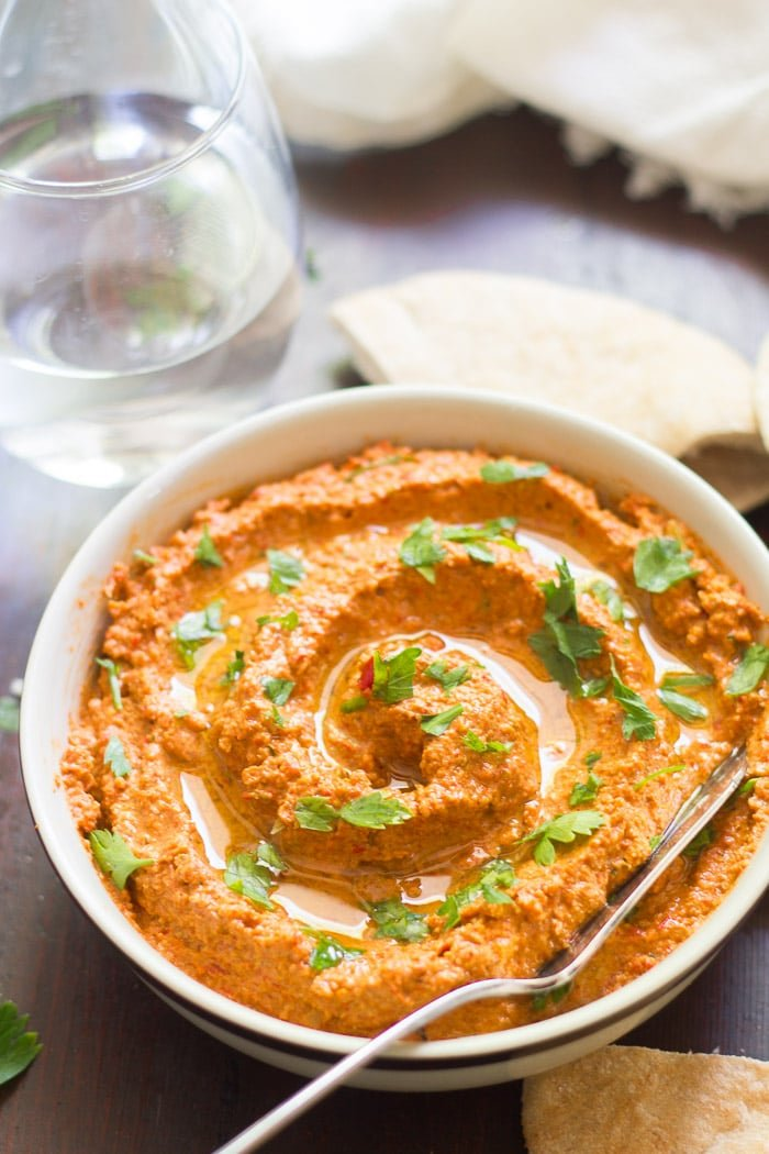 Muhammara in a Bowl with Water Glass and Pita Bread in the Background
