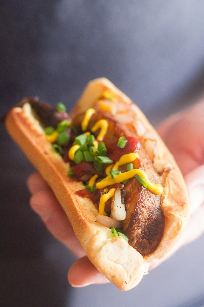 Hand Holding a Portobello Mushroom Hot Dog on a Bun