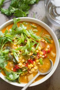 Close Up of a Bowl of Vegan Corn Chowder Topped with Scallions and Cilantro