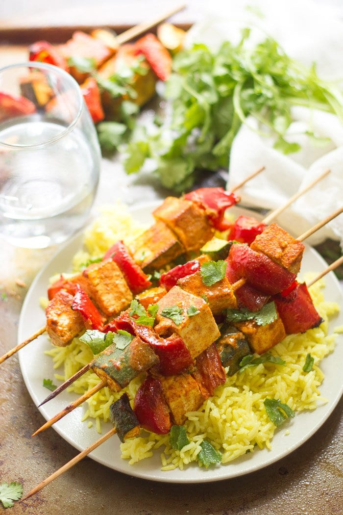 Plate of Mediterranean-Spiced Tofu Kebabs with Water Glass and Fresh Cilantro in the Background