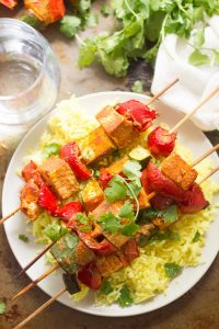 Mediterranean-Spiced Tofu Kebabs Over Rice on a Plate