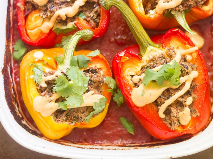 Black Bean Burger Stuffed Peppers in a Baking Dish with Tomato Sauce