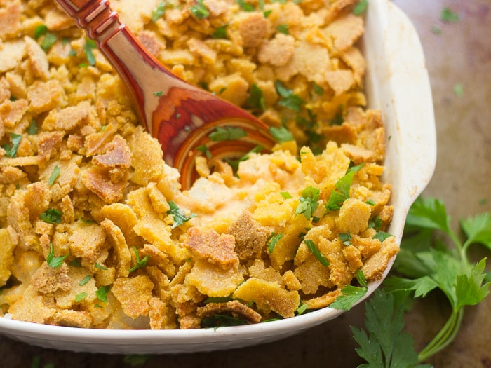Cheesy Vegan Corn Flake Potato in a Casserole Dish with Wooden Spoon
