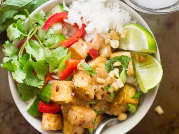 Close Up of a Buddha Bowl with Tofu, Rice, Peanut Sauce, Lime Wedges, and Fresh Herbs