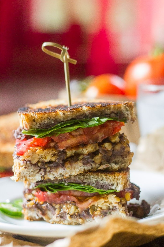 Two Halves of a Grilled Black Bean & Tempeh Bacon Sandwich Stacked on a Plate