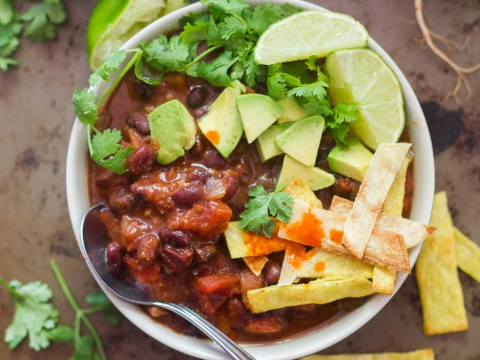 Overhead View of a Bowl of Black Bean Tortilla Soup Topped with Cilantro, Lime, Avocado, and Tortilla Strips