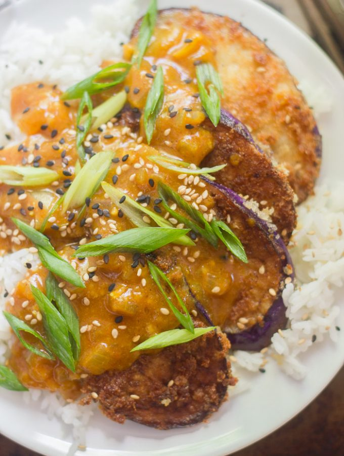 Eggplant Katsu Curry Topped with Sesame Seeds and Scallions on a Plate Over Rice