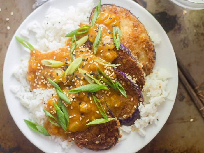 Overhead View of a Plate of Eggplant Katsu Curry with Chopsticks at the Side