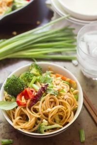 Bowl of Stir-Fried Hoisin Noodles with Chopsticks, Water Glass, and Bunch of Scallions in the Background
