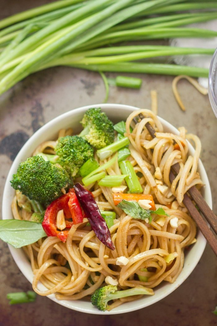 Bowl of Stir-Fried Hoisin Noodles with a Bunch of Noodles Wrapped Around the End of Two Chopsticks