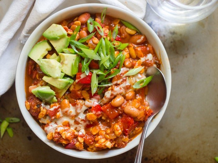A Bowl of Tempeh Chili Topped with Scallions and Avocado