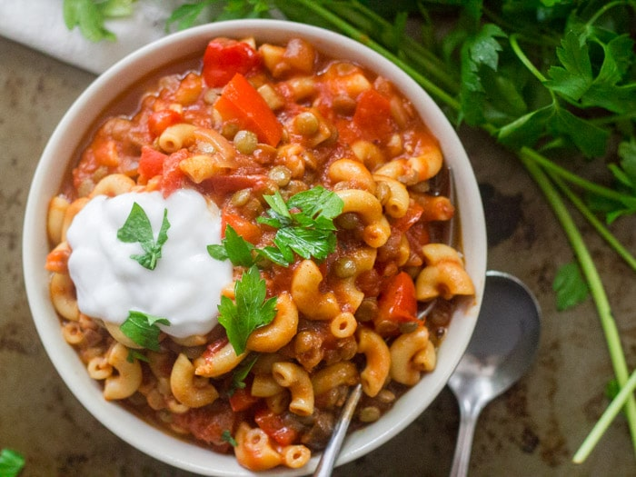 Bowl of Vegan American Goulash with a Spoon and Bunch of Parsley