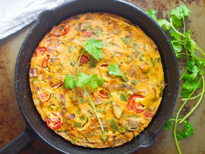 Taco-Spiced Vegan Frittata in a Skillet with a Sprig of Cilantro on Top