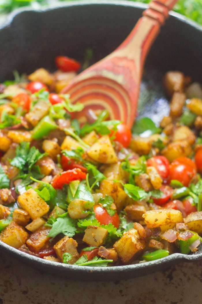 Potatoes and Peppers Sizzling in a Skillet with Wooden Spoon