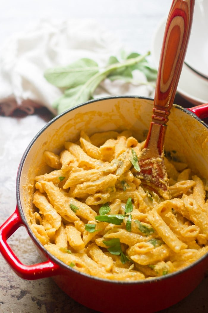 Pot of Creamy Vegan Pumpkin Pasta with Wooden Spoon
