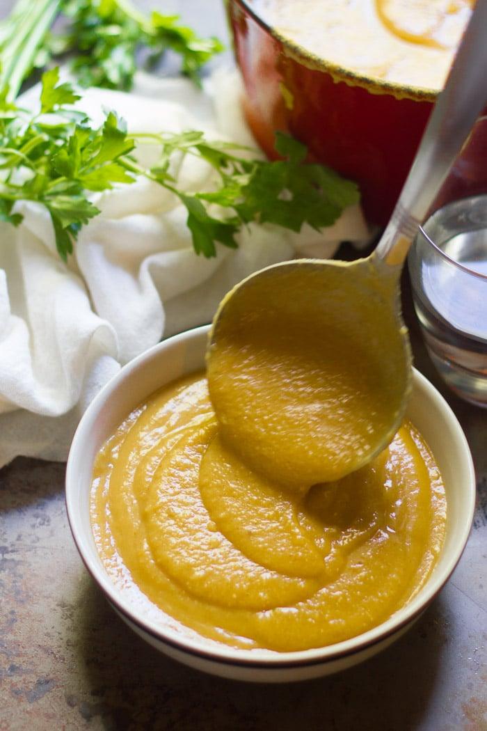Ladle Pouring Red Lentil Butternut Squash Soup into a Bowl