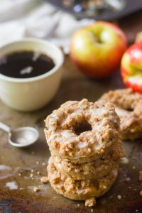 Stack of 3 Vegan Apple Crumble Doughnuts with Coffee Cup, Spoon, and Apples in the Background