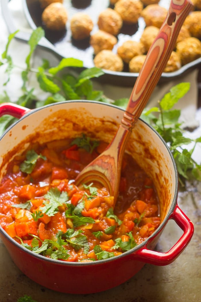 Stew with Fresh Herbs and Wooden Spoon in a Red Pot
