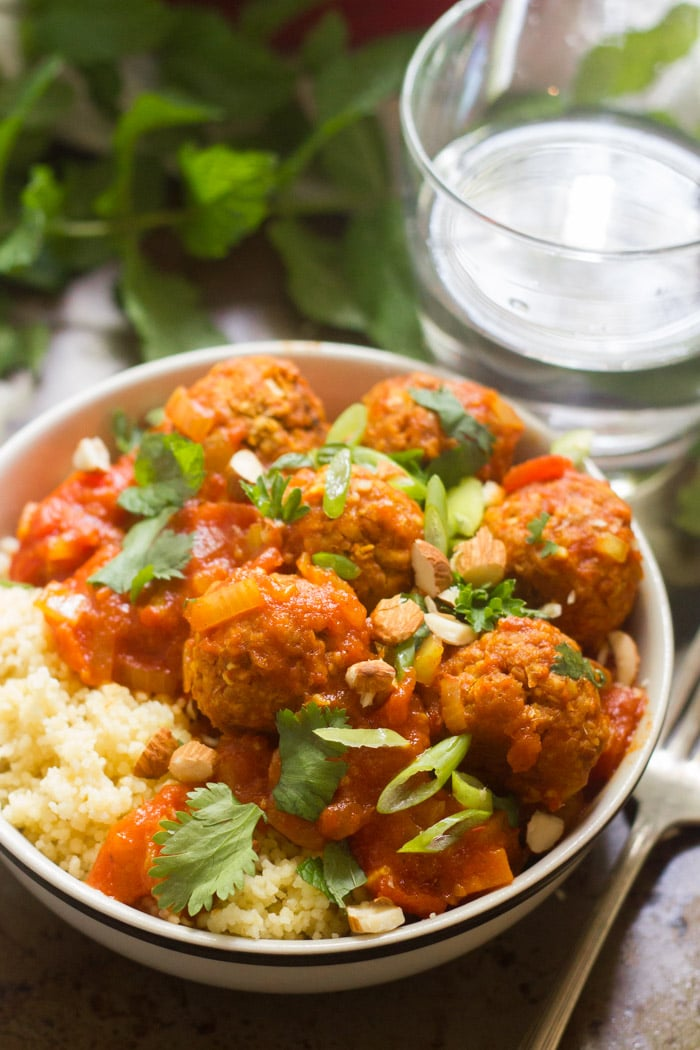 Bowl of Vegan Moroccan Meatball Stew and Couscous with Water Glass and Fresh Mint in the Background